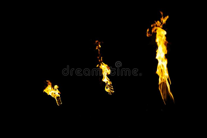 Three flames of a torches in the dark. On a black background, only the fires is visible stock image