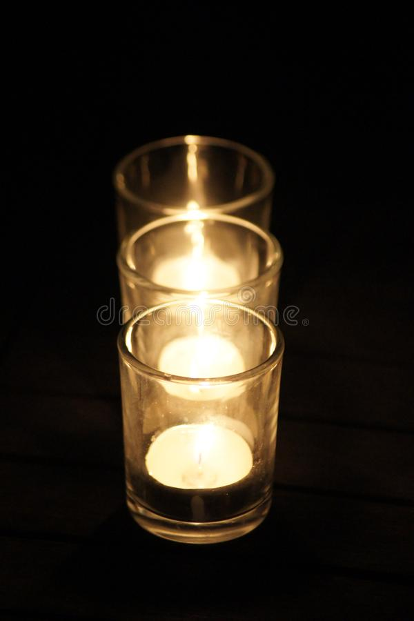 Three flickering candles light up the night. royalty free stock photo