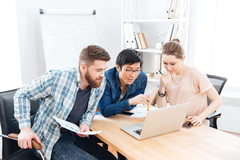 Three focused businesspeople working with laptop in office. Three focused young businesspeople working with laptop in office together stock images