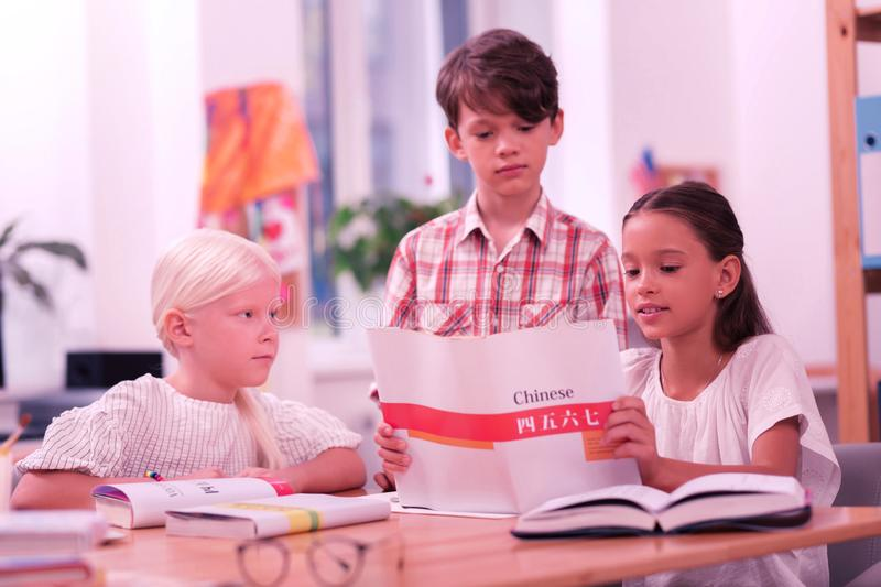 Three focused pupils reading a chinese workbook. Discovering new. Three focused children reading a chinese workbook, girls sitting at the desk and a boy royalty free stock photos