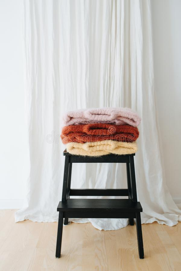 Three folded multi-colored sweaters lie on stepping stool in front of a curtain stock photos