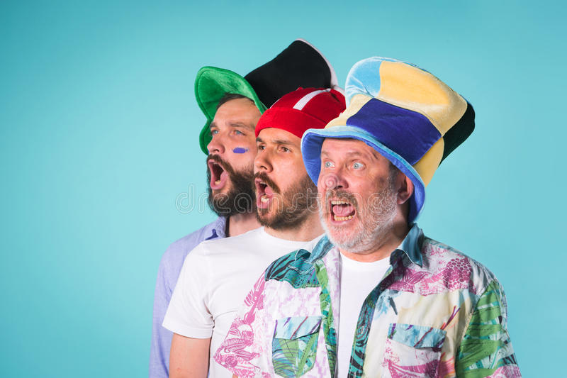 The three football fans singing the national anthem over blue. Background stock images