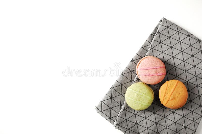 Three france cakes on grey kitchen towel. Towel with ornament lines, boxes. Macaroons on table. Green, pink and orange sweets in c royalty free stock photography