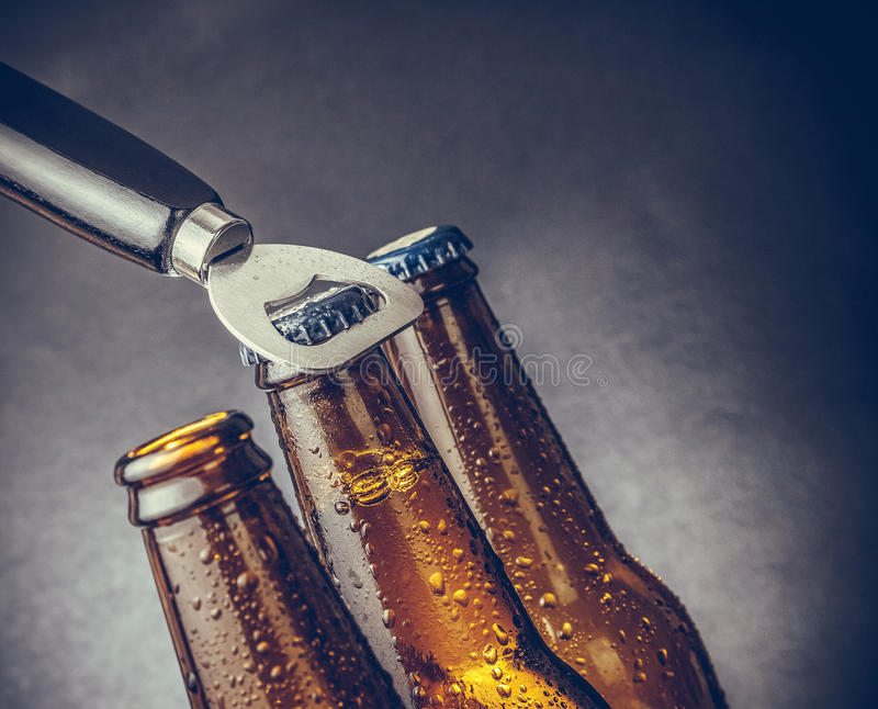 Three fresh cold beer ale bottles with drops and stopper open with bottle opener stock image