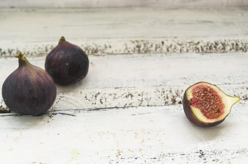 Three fresh figs on a wooden white table. One fig is cut in halves and its flesh is visible. Located in a group. The concept of urge royalty free stock photos