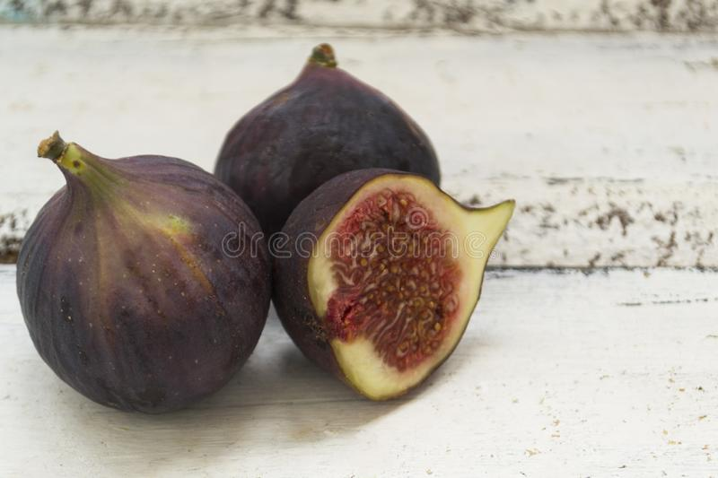 Three fresh figs on a wooden white table. One fig is cut in halves and its flesh is visible. Located in a group. The concept of urge royalty free stock photography