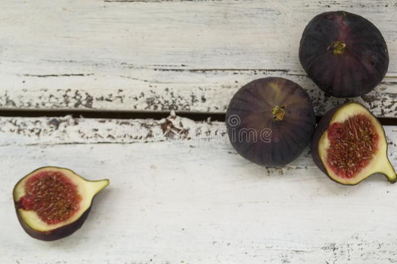 Three fresh figs on a wooden white table. One fig is cut in halves and its flesh is visible. Located in a group. The concept of urge royalty free stock photo