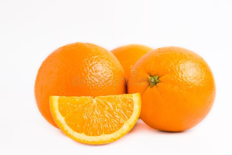 Three fresh juicy oranges and one slice lobule isolated on white background. Close photo stock photography