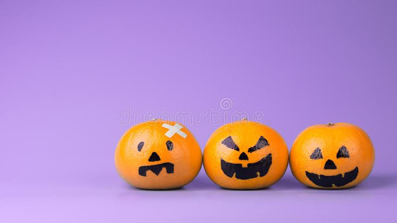 Three Fresh Oranges with Halloween Pumpkins painted face. Easy stock photos