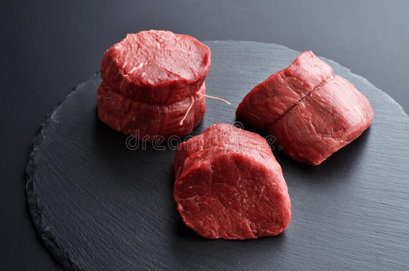 Three fresh raw Prime Black Angus beef steaks on stone background. Three fresh raw Prime Black Angus Tenderloin beef steaks on stone background. Selected focus royalty free stock images