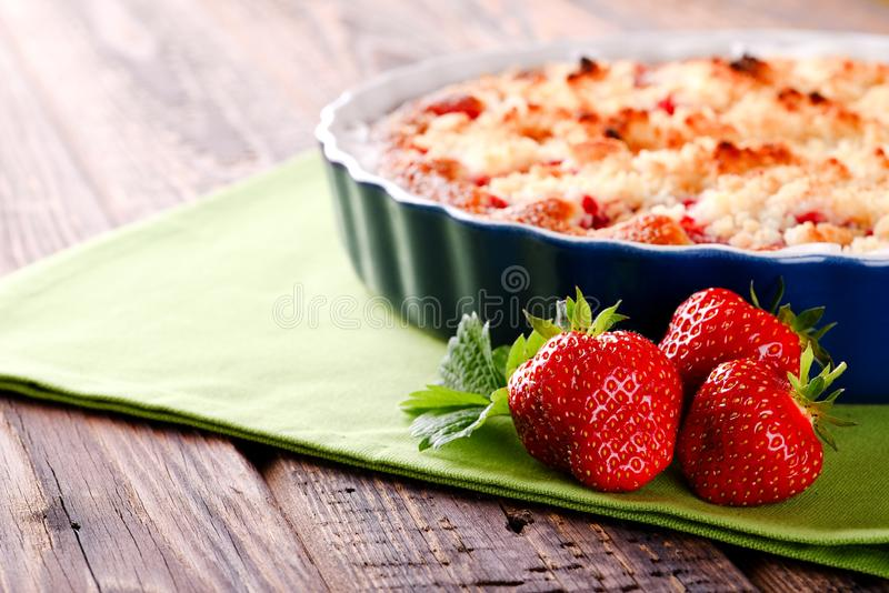 Three fresh red strawberries in front of fruit pie on green towel stock images