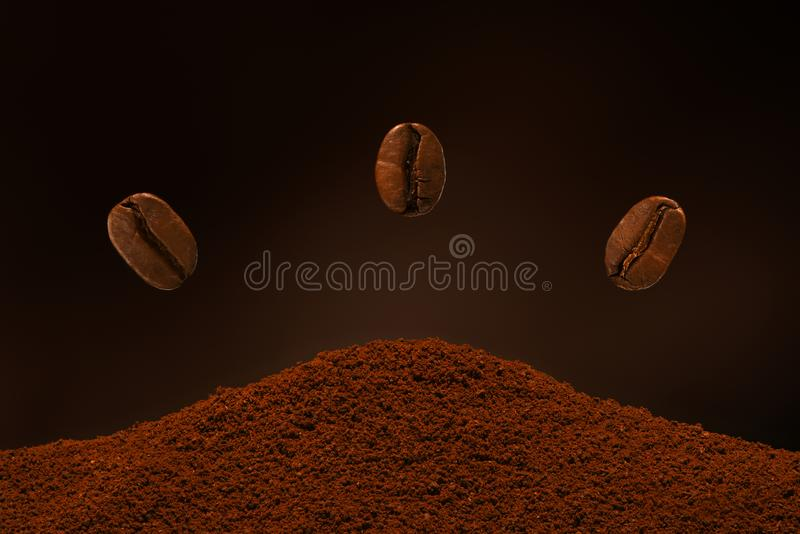Three fresh roasted coffee beans fly over a handful of ground coffee on a brown background. Postcard, banner royalty free stock photo