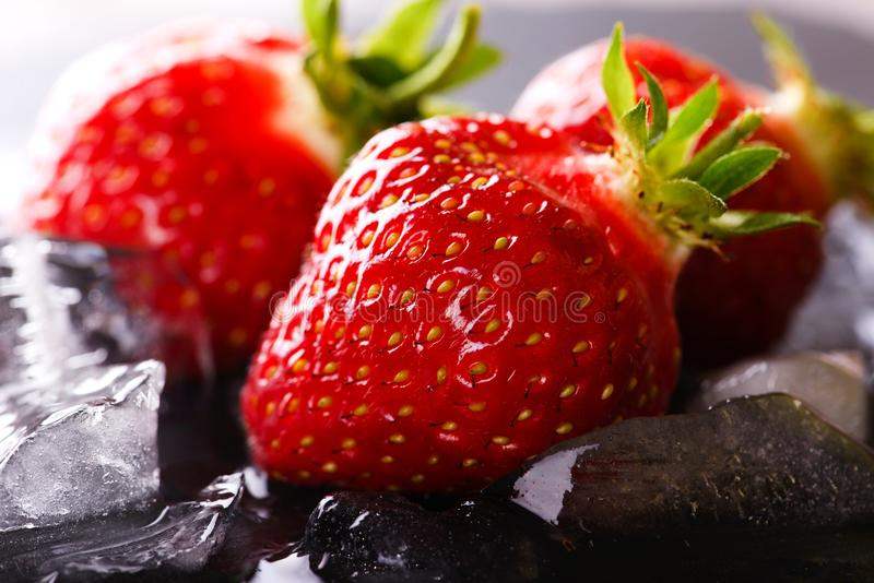 Three fresh strawberries on slate stone with ice stock photography