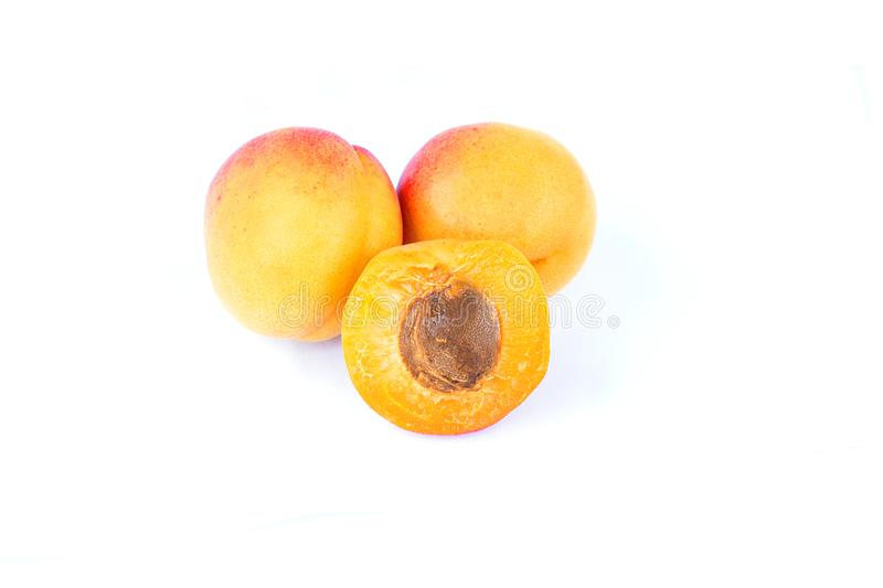 Three fresh sweet apricot fruit, whole and half, group of juicy ripe apricots closeup, isolated on the white background stock image