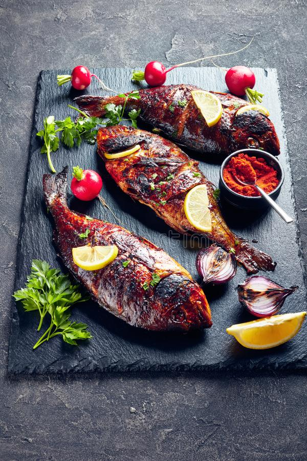 Three freshly fried dorado fish with radish royalty free stock photo