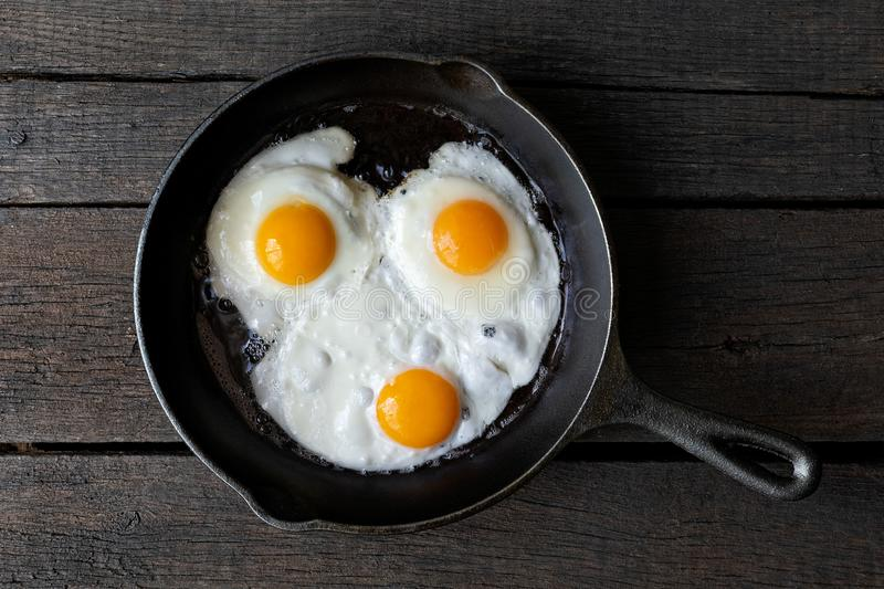 Three fried eggs in cast iron frying pan isolated on dark painted wood from above. stock image