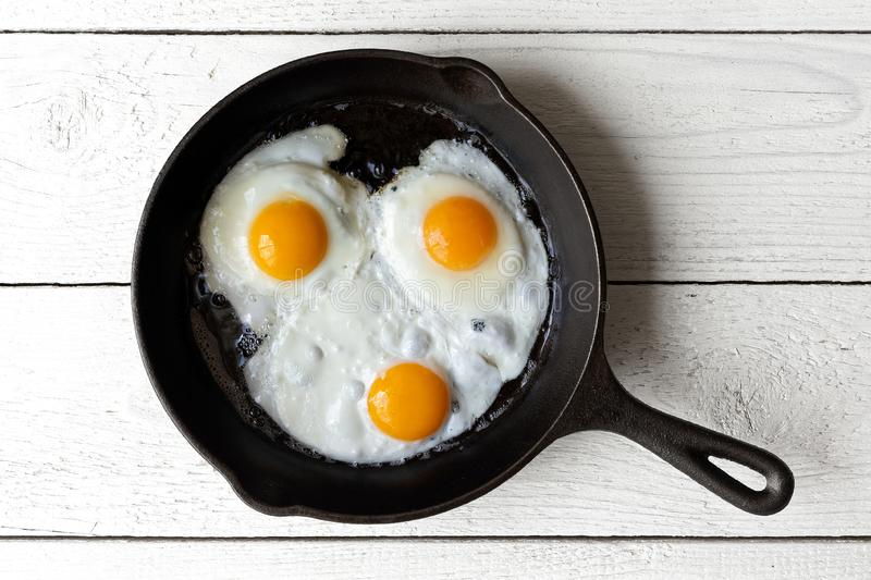 Three fried eggs in cast iron frying pan isolated on white paint stock images