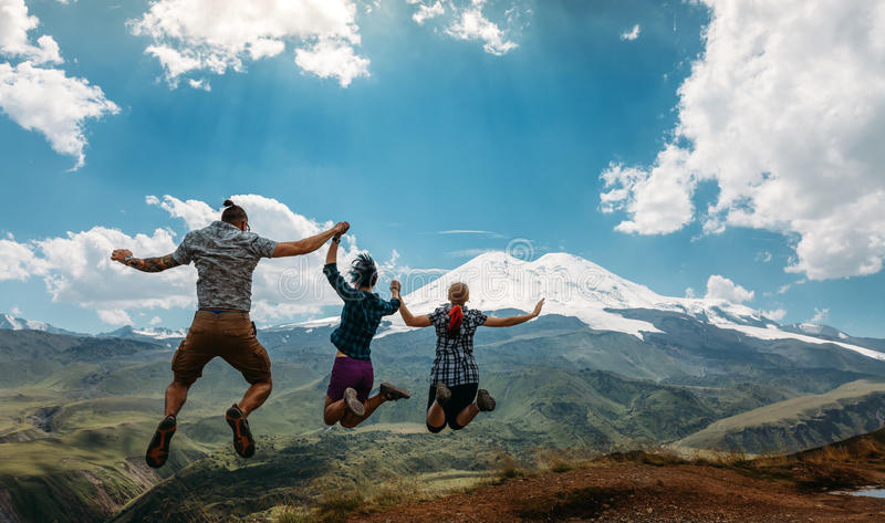 Three Friend Jumping Holding Hands Mountains Elbrus Landscape On Background. Lifestyle Travel Happy Emotions Success Concept Summe stock photos