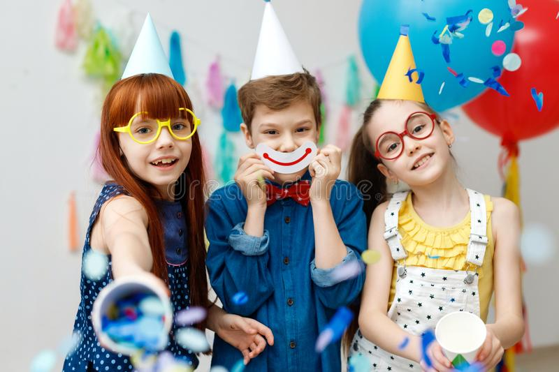 Three friendly children in festive cone caps and big eyewear, stand in decorative room with balloons, have fun together royalty free stock image