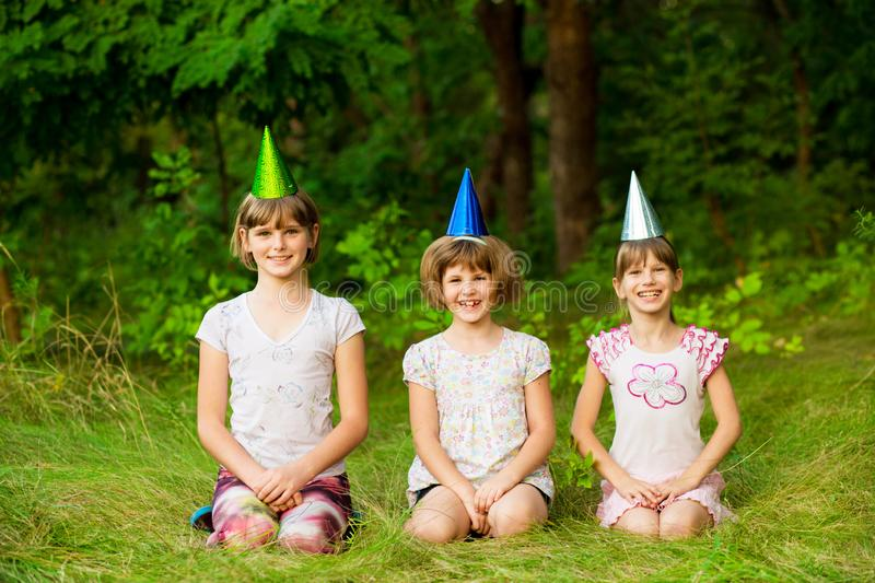 Three friendly children in festive cone caps, sit on grass, have fun together as celebrate birthday royalty free stock photos