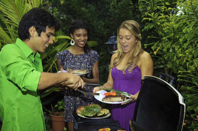 Three friends at a barbecue. Party in their tropical garden in hawaii cooking steaks on the grill royalty free stock photography