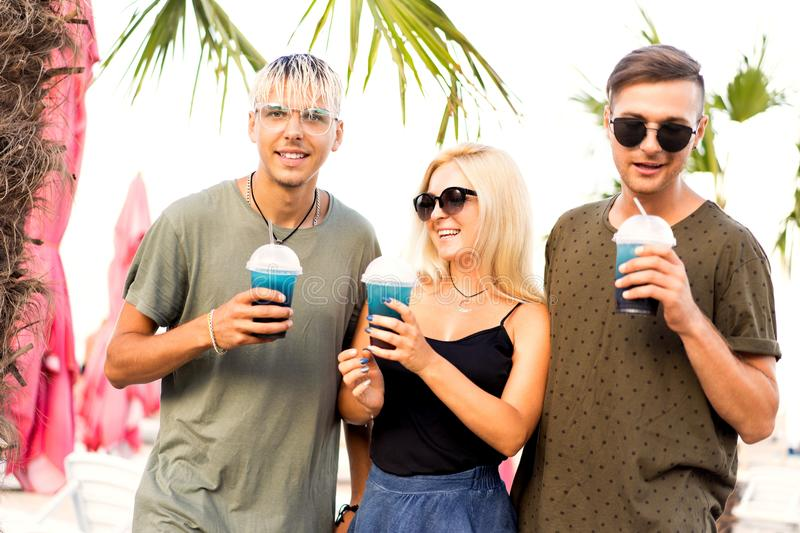 Three friends cheerful company rest on a tropical beach and drink cocktails, very, magazine concept.  royalty free stock images