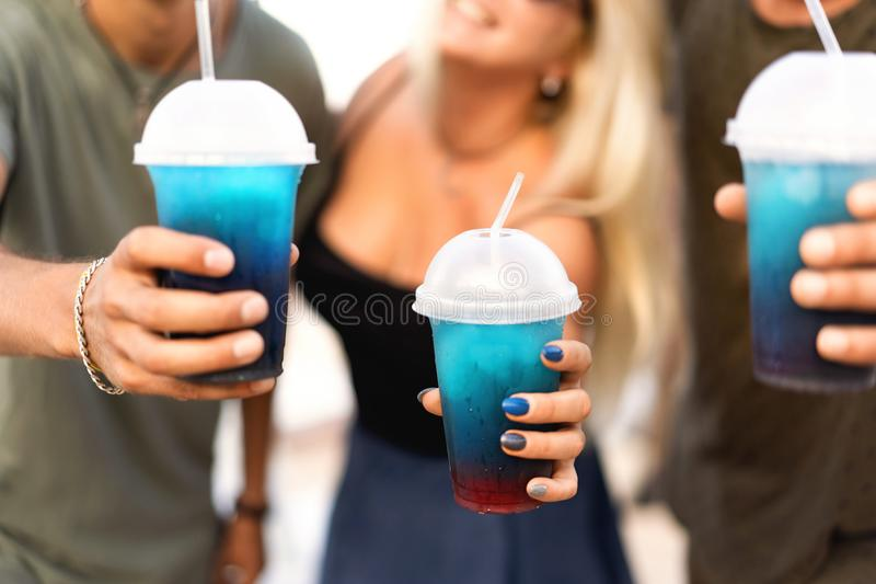 Three friends cheerful company rest on a tropical beach and drink cocktails, very, magazine concept.  royalty free stock photography