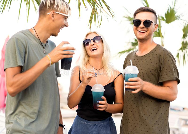 three friends cheerful company rest on a tropical beach and drink cocktails, very, magazine concept royalty free stock images