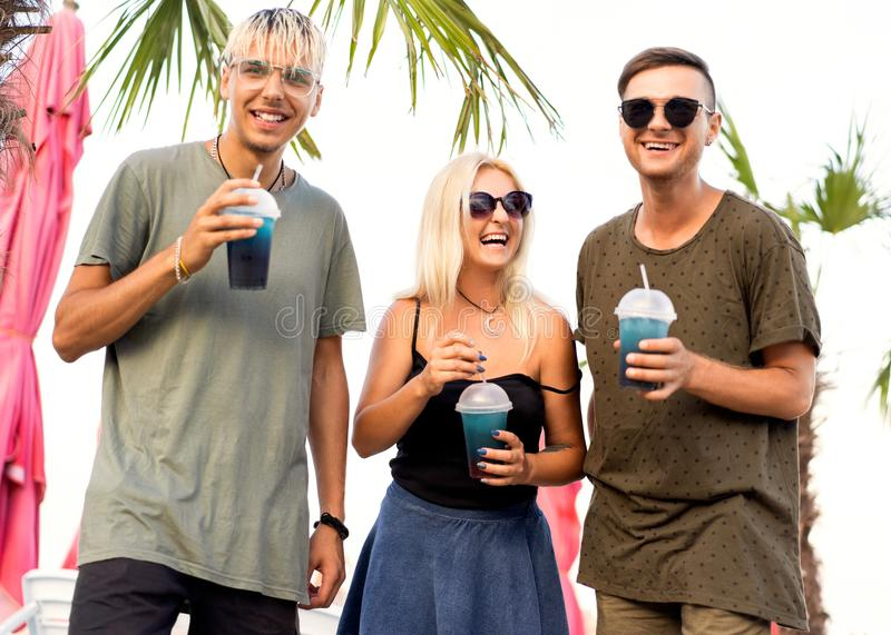 three friends cheerful company rest on a tropical beach and drink cocktails, very, magazine concept royalty free stock photography