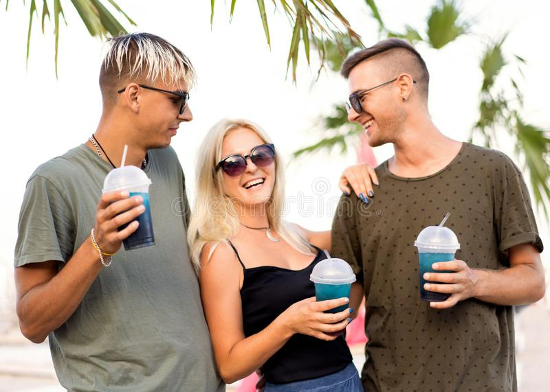 Three friends cheerful company rest on a tropical beach and drink cocktails, very, magazine concept. Three friends cheerful company rest on a tropical beach and stock photo