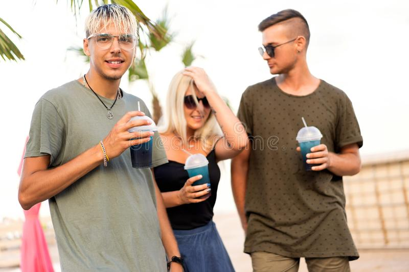 Three friends cheerful company rest on a tropical beach and drink cocktails, magazine concept.  stock images