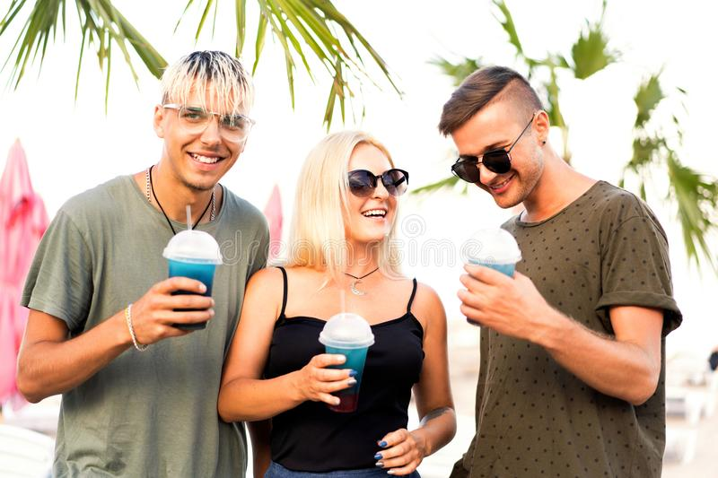 Three friends cheerful company rest on a tropical beach and drink cocktails, very, magazine concept.  stock image
