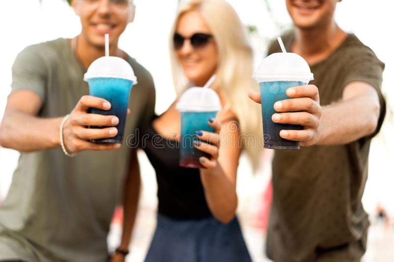 Three friends cheerful company rest on a tropical beach and drink cocktails, very, magazine concept.  royalty free stock photo