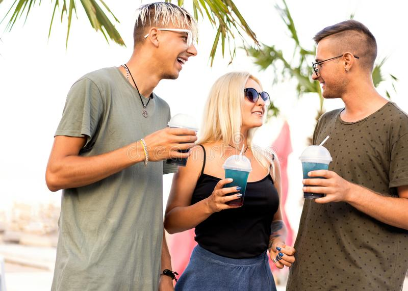 three friends cheerful company rest on a tropical beach and drink cocktails, very, magazine concept stock photos