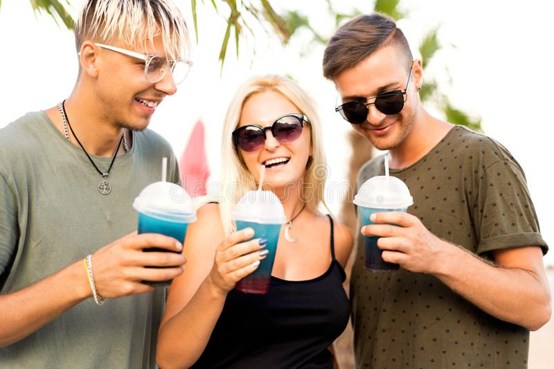 Three friends cheerful company rest on a tropical beach and drink cocktails, very, magazine concept stock images