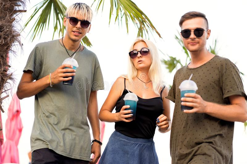 Three friends cheerful company rest on a tropical beach and drink cocktails; very; magazine concept.  royalty free stock photos