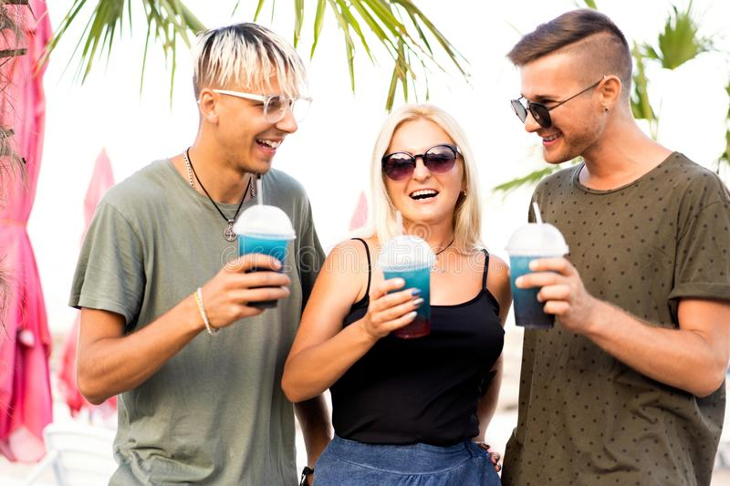 Three friends cheerful company rest on a tropical beach and drink cocktails, very, magazine concept.  royalty free stock image