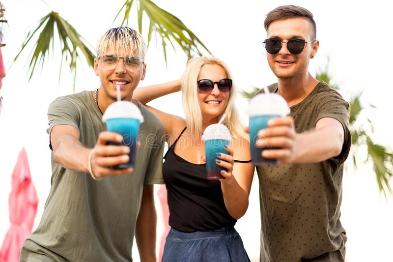 Three friends cheerful company rest on a tropical beach and drink cocktails, very, magazine concept.  stock photography