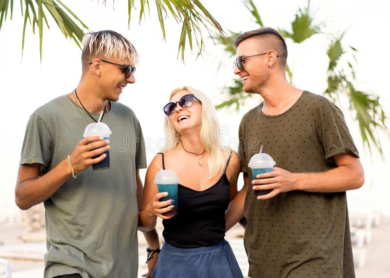 Three friends cheerful company rest on a tropical beach and drink cocktails; very; magazine concept.  stock photography