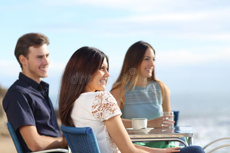 Three friends contemplating ocean from a bar royalty free stock images