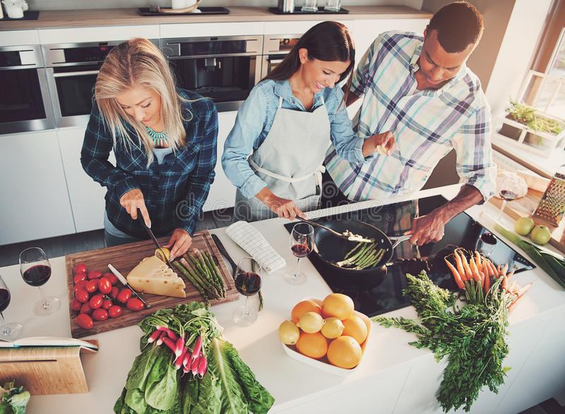 Three friends cooking at kitchen stock photo