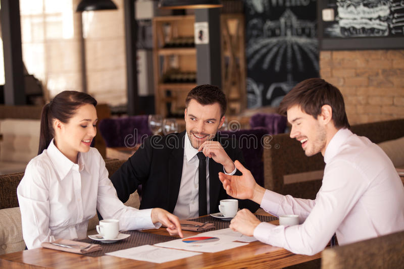 Three Friends Discuss Graph Lying On Table At Cafe. Stock ...