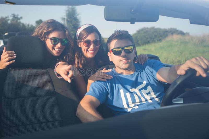 Three friends driving around in a convertible exploring stock photo