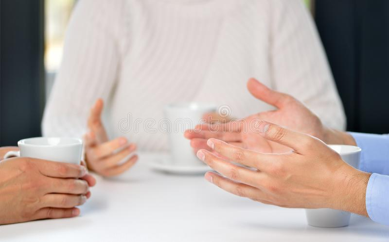 Three friends talking in a bar. Three friends hands talking in a bar stock photography