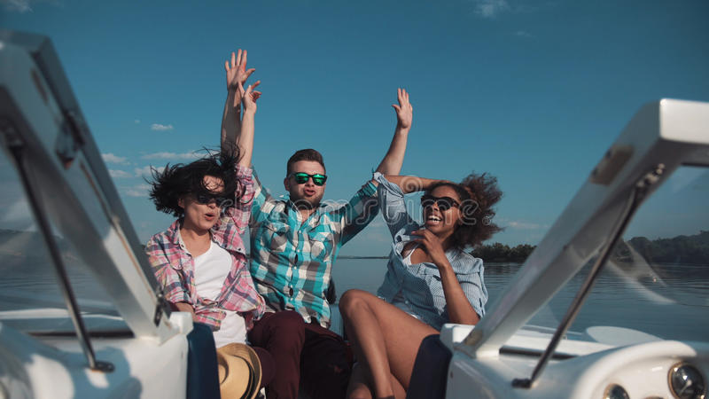 Three friends having fun on boat. Man with two girl celebrating while sailing on boat and enjoying day royalty free stock photo