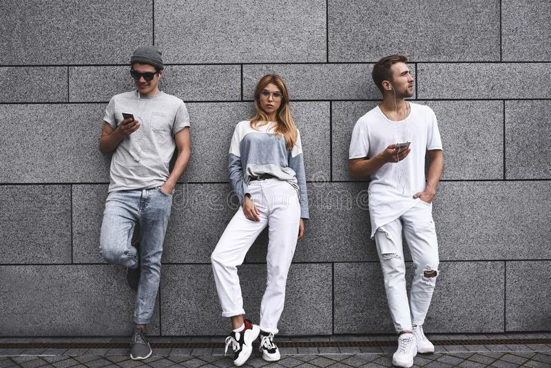 Three friends leaning to a wall and ignoring each other. royalty free stock image