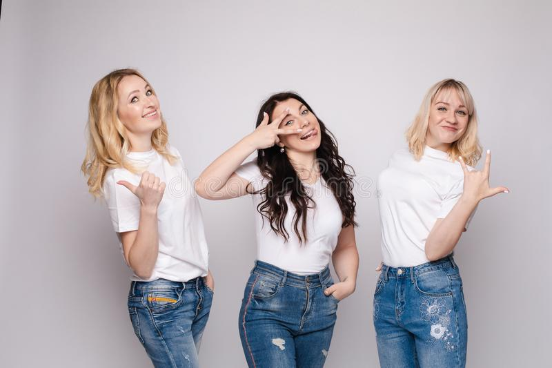 Three friends looking at camera and shouting in surprise. Three female friends looking at camera and shouting in surprise on white  background in studio. Amazed royalty free stock images