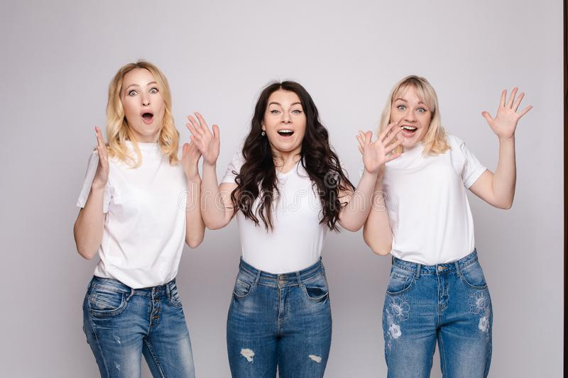Three friends looking at camera and shouting in surprise. Three female friends looking at camera and shouting in surprise on white  background in studio. Amazed royalty free stock image
