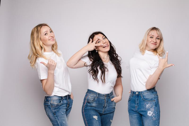 Three friends looking at camera and shouting in surprise. Three female friends looking at camera and shouting in surprise on white  background in studio. Amazed royalty free stock photos