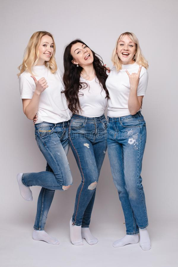 Three friends looking at camera and shouting in surprise. Three female friends looking at camera and shouting in surprise on white  background in studio. Amazed stock photo